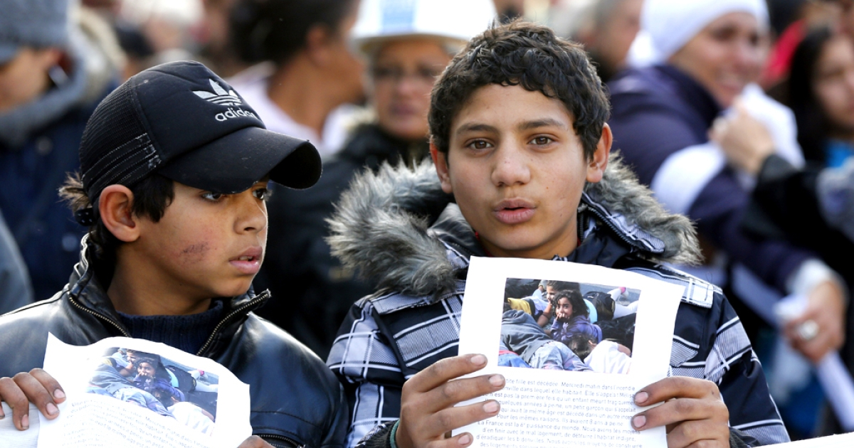 Two children hold a picture of Melissa, an eight-year old Bulgarian Roma girl who perished in a fire that destroyed her camp in the Paris suburbs earlier in the week, during a white march commemorating her death, in Bobigny, near Paris, on February 16, 2014.</p>