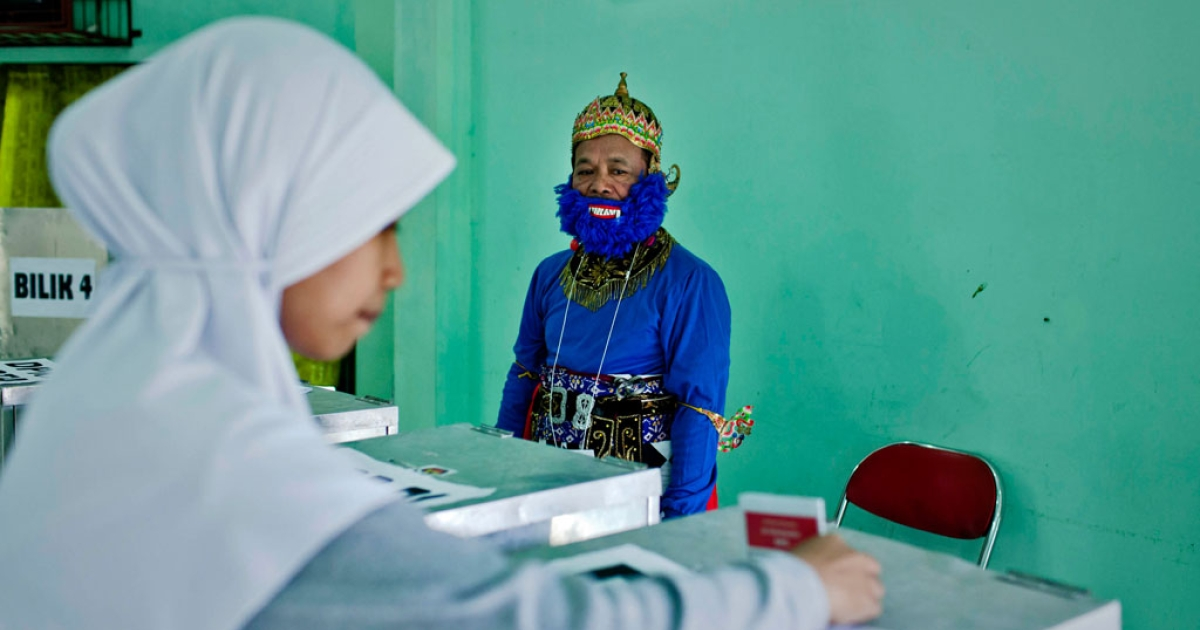 An election officer in traditional wayang orang costume looks at a woman as she votes at polling station during the legislative elections on April 9, 2014 in Yogyakarta, Indonesia.</p>