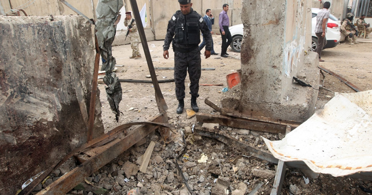 An Iraqi policeman inspects the site of a suicide bombing at the university of Imam Kadhim University in the capital Baghdad on April 20, 2014.</p>