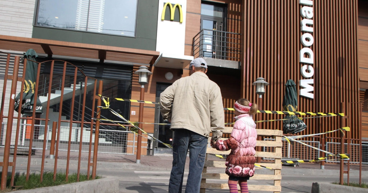 A man and a little girl look at a closed McDonald's in the Crimean capital Simferopol on April 4, 2014.</p>