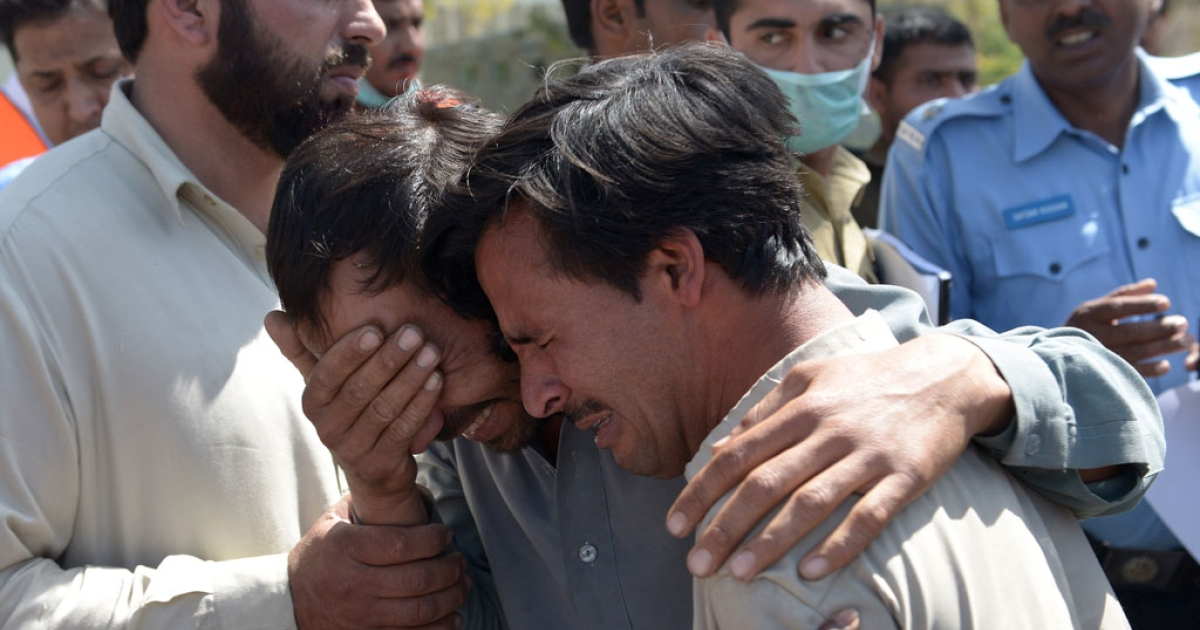Pakistani mourners grieve the death of relatives at a hospital in Islamabad on April 9, 2014.</p>
