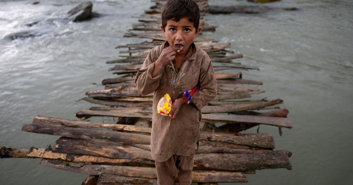 An Afghan refugee boy looks as he crosses a temporary wooden bridge at Jalala refugee camp in district Mardan on April 2, 2014.</p>