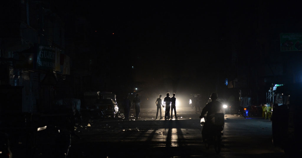 This picture taken on Feb. 24, 2013 shows Pakistani youth crossing a street during a nationwide power blackout in Karachi.</p>