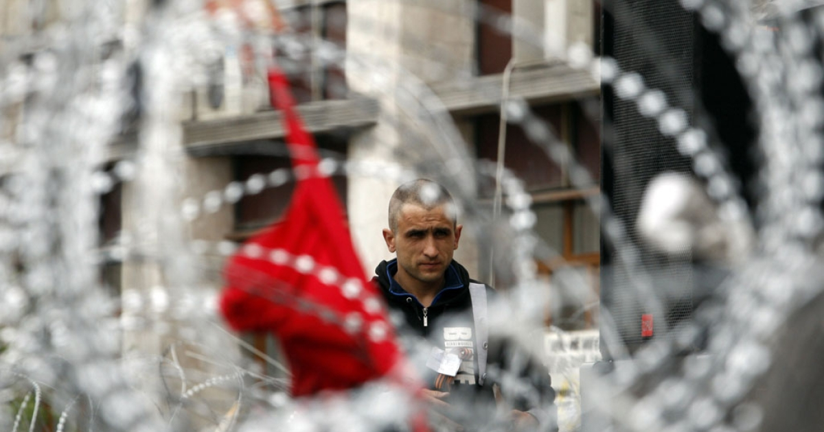 A pro-Russian activist is pictured through barbed wire as he guards a barricade outside the regional administrative building in the eastern Ukrainian city of Donetsk.</p>