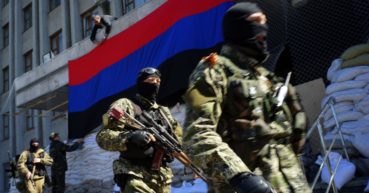 A pro-Russian activist hangs a flag of the so-called 'People's Republic of Donetsk' on the regional administration building seized by separatists in the Ukrainian city of Slavyansk on April 21, 2014.</p>