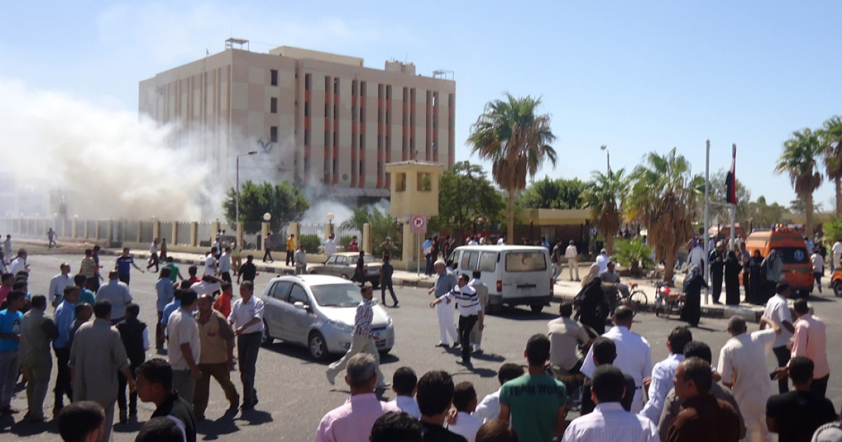 Bystanders gather at the Egyptian provincial police headquarters in the Sinai peninsula following a car bomb explosion which killed three policemen on Oct. 7, 2013.</p>