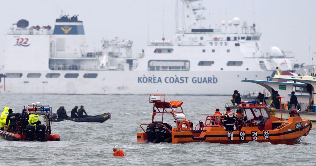South Korean coast guards and rescue workers are seen at the accident site of the capsized South Korean ferry Sewol in Jindo on April 22, 2014.</p>