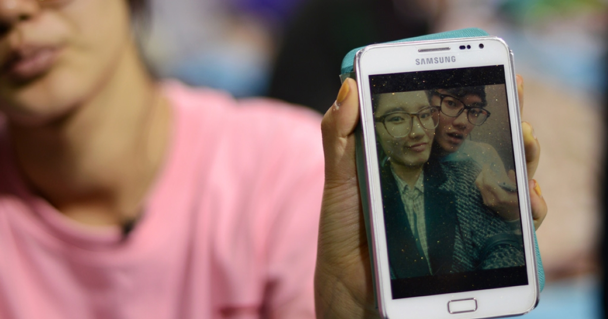 Hana Kim, 22, shows a photo of her brother, 16-year-old Kim Dong Hyup, missing after the sinking of the South Korean ferry