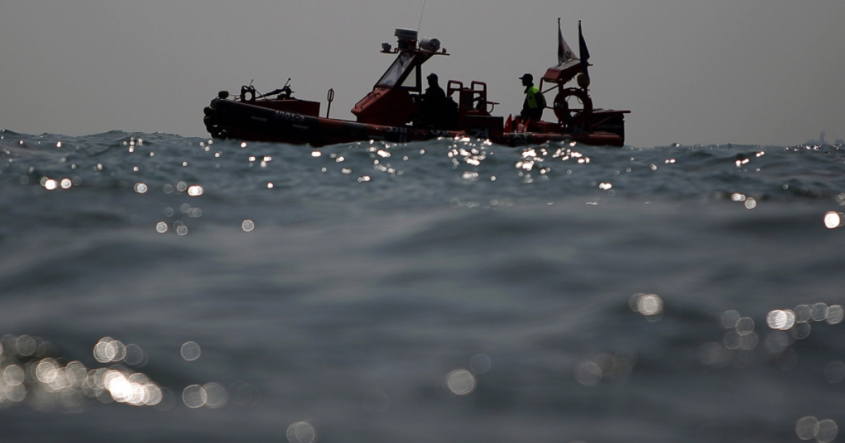 The South Korean coast guard searches for missing passengers at the site of the sunken ferry off the coast of Jindo Island on April 20, 2014.</p>