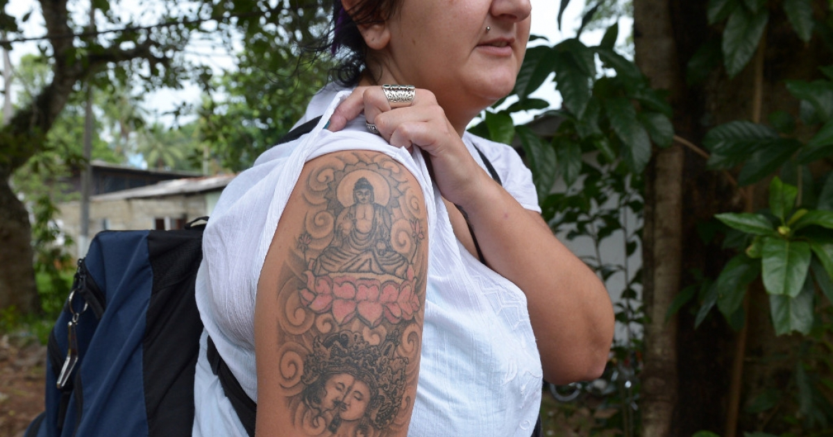 British tourist Naomi Coleman displays a tattoo of the Buddha on her arm in Colombo, Sri Lanka.</p>