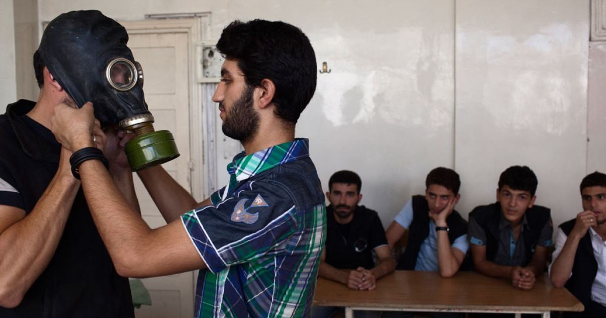 An Aleppo University student shows Syrian citizens how to put on gas masks.</p>