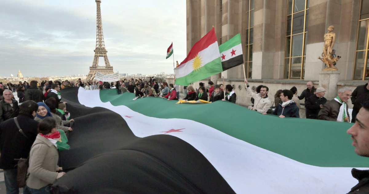 People hold a former Syrian national flag used by the opposition as they gather in front of the Eiffel tower on March 15, 2014 in Paris.</p>