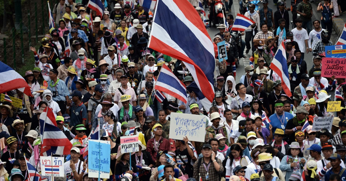 Anti-government protesters wave national flags during a march in downtown Bangkok on March 25, 2014.</p>