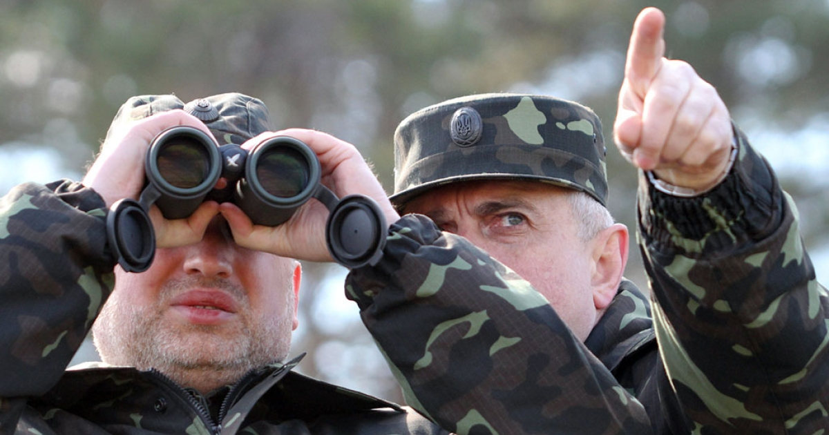 Acting Minister of Defense of Ukraine Michail Koval (R) and Olexander Turchynov, speaker of the parliament and the interim president, attend military exercises on the shooting range in Desna, Chernigiv region on April 2, 2014.</p>