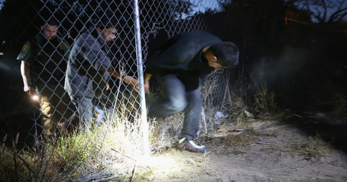 A US Border Patrol agent detains undocumented immigrants who had crossed from Mexico into the United States on April 11, 2013, in Mission, Texas.</p>