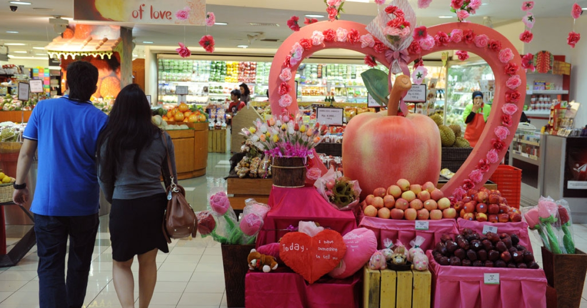 An Indonesian couple enters a grocery shop decorated with a mock up apple and heart to celebrate Valentine's Day in Jakarta on Feb. 14, 2012.</p>