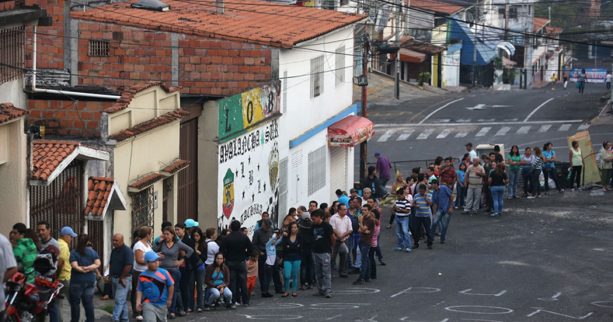 People line up before sunrise to buy basic foodstuffs at a supermarket on March 8, 2014 in San Cristobal, Venezuela.</p>
