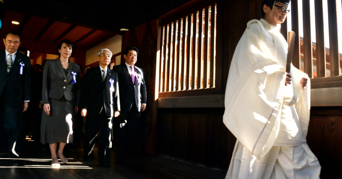 Japanese lawmakers follow a Shinto priest (R) during a visit to the controversial Yasukuni shrine to honor the war dead at the shrine's spring festival in Tokyo on April 22, 2014.</p>