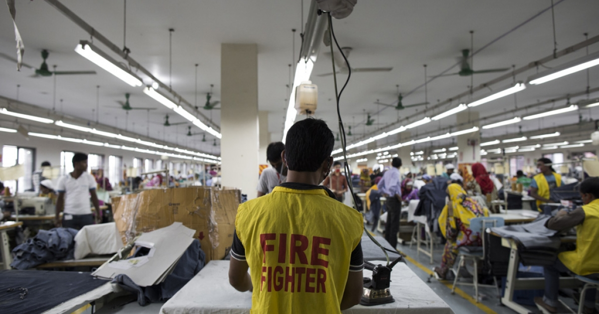 A garment worker wearing a fire fighter vest at the Azim and Sons (Pvt.) Ltd. factory.</p>