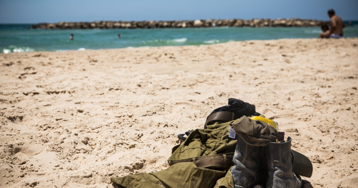 An Israeli soldier's uniform and boots sit in the sand on Ashkelon Beach during a 12-hour ceasefire in late July.</p>