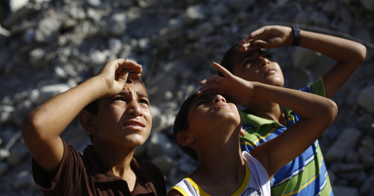 Palestinian children look up at an Israeli plane in Beit Lahia in the northern Gaza Strip on August 4, 2014. Israel will hold its fire in most of the Gaza Strip for a seven-hour 'humanitarian window,' the military said, four weeks into its bloody conflict with Hamas.</p>