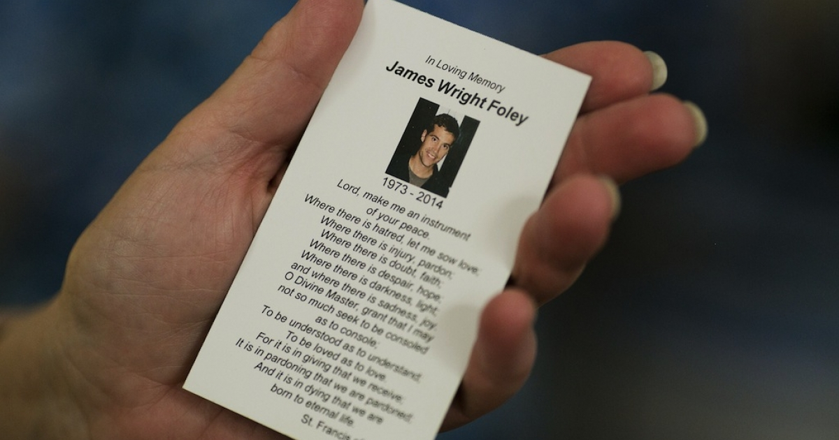 A parishioner holds a prayer card in memory of James Foley after a Catholic mass at Our Lady of the Holy Rosary parish August 24, 2014, in Rochester, New Hampshire. The family and friends of murdered US journalist James Foley attended the memorial mass and offered prayers for the safety of his fellow hostages in Syria.</p>