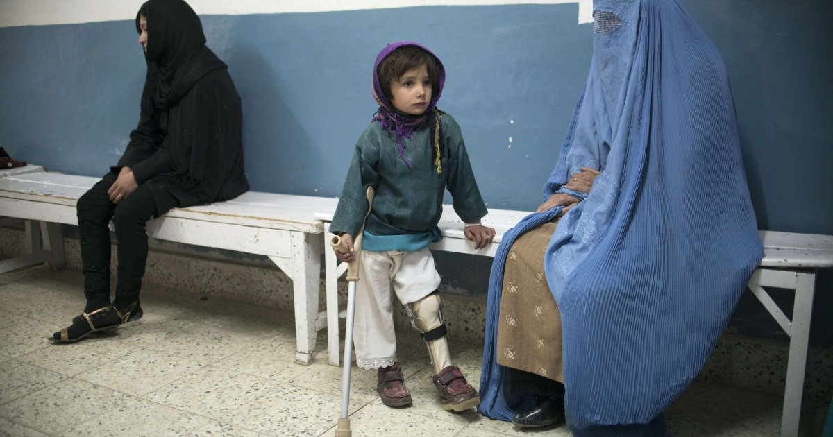 Halima, aged 5, rests after practicing walking with a crutch as her mother looks on at the International Committee for the Red Cross Orthopaedic Center in Gulbahar, Afghanistan, on Jan. 14, 2014.</p>