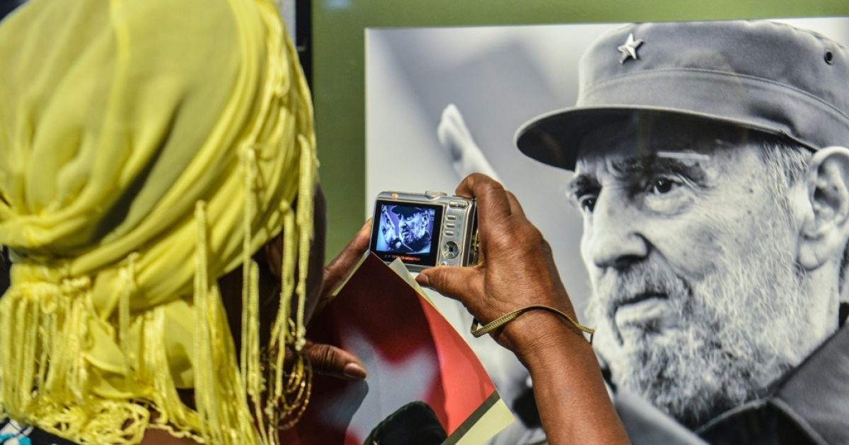 A woman takes a picture of a photo of former Cuban President Fidel Castro during the opening of a photography exhibition on him in Havana. Castro turns 88 years old on Wednesday, Aug. 13.</p>