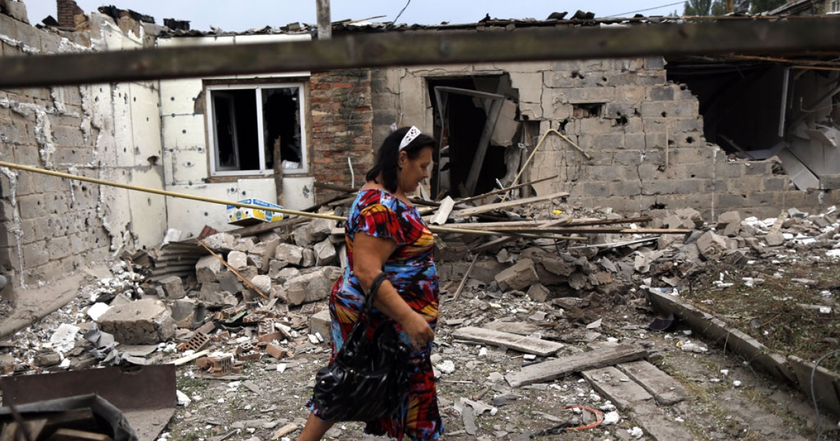 A woman walks past a damaged house in Donetsk on Aug. 11, 2014.</p>