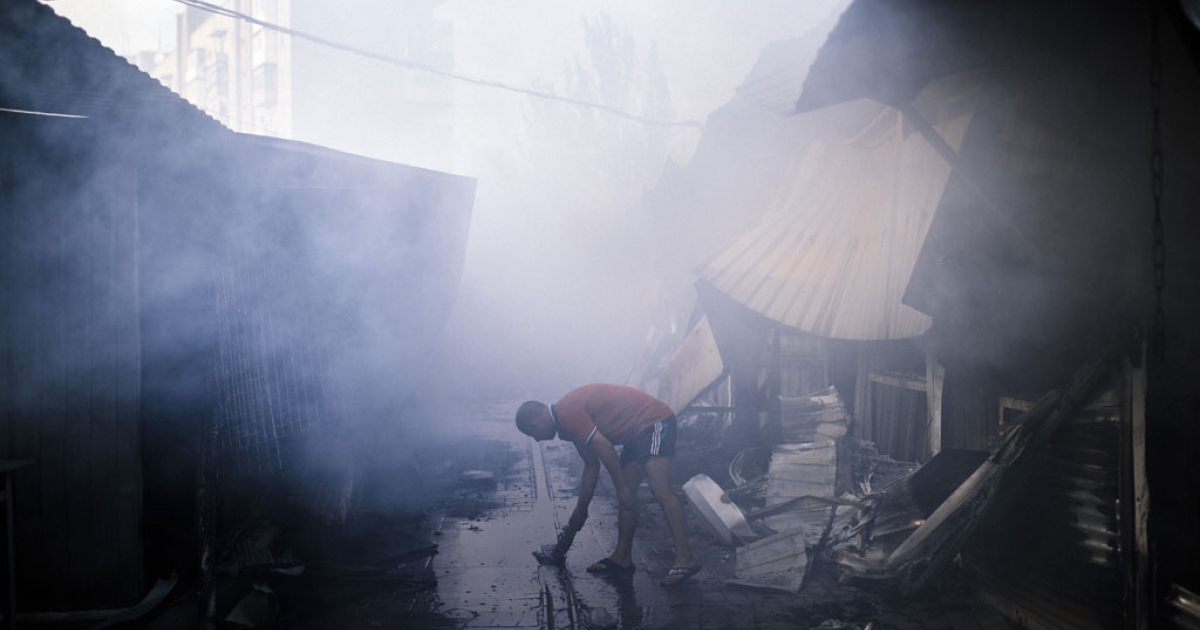 A man collects water to fights a fire after the shelling of an open market in the town of Yasynuvata near the rebel stronghold of Donetsk on Aug. 12, 2014.</p>