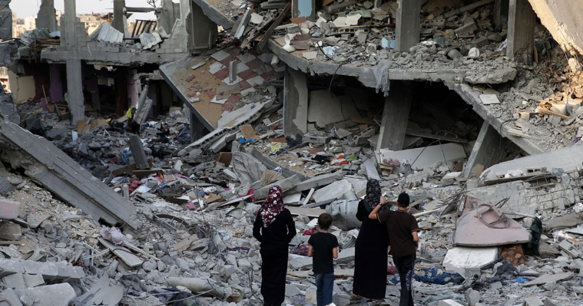 Palestinians walk in the rubble of destroyed houses in Gaza City's Shejaiya neighborhood on Aug. 17, 2014.</p>