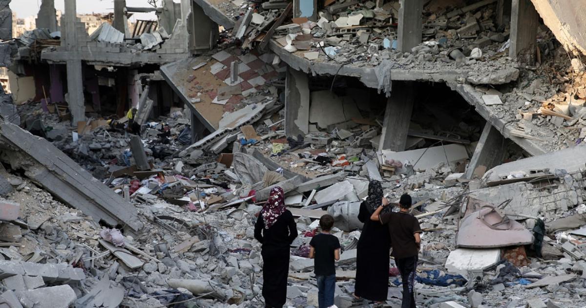 Palestinians walk in the rubble of destroyed houses in Gaza City's Shejaiya neighborhood on Aug. 17, 2014.</p>