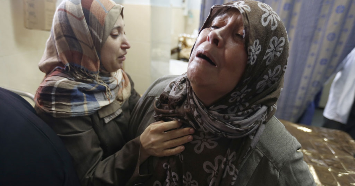 Palestinian women from the al-Dalo family react at the Al-Shifa hospital in Gaza City, on Aug. 20, 2014, after victims were brought to the morgue to be prepared for burial.</p>