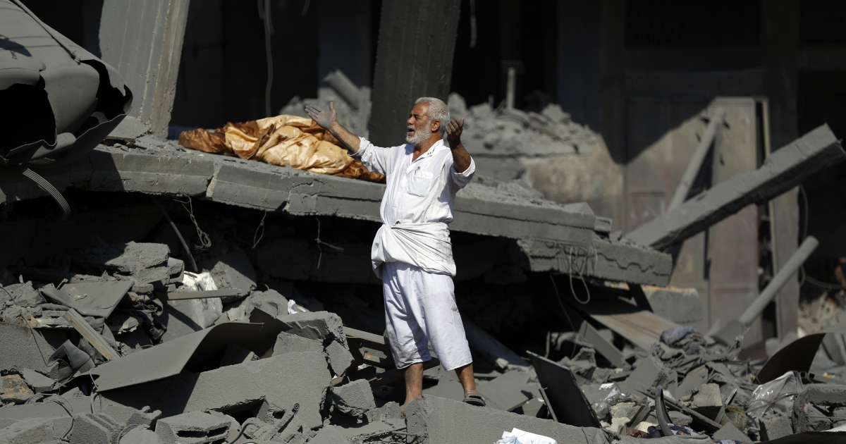 A Palestinian man reacts as he stands on the rubble of his home in Jabalia in the northern Gaza Strip on Aug. 1, 2014</p>