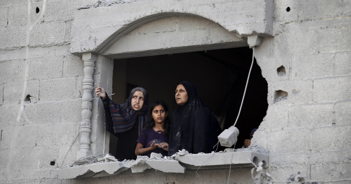 Palestinians look at the wreckage from a damaged window following an Israeli strike, in Rafah, southern Gaza Strip, Aug. 2, 2014.</p>