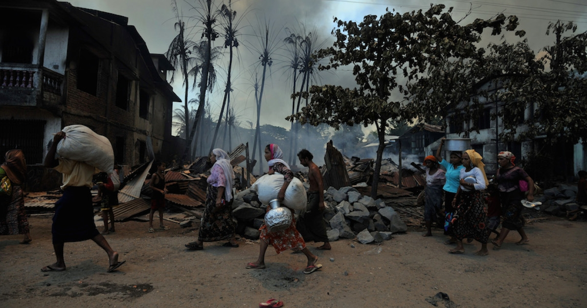 Muslim residents carry their belongings as they evacuate their houses amid ongoing violence in Sittwe, capital of Myanmar's western state of Rakhine, on June 12, 2012. In the newly liberalized country, vicious rumors are spreading via social media.</p>