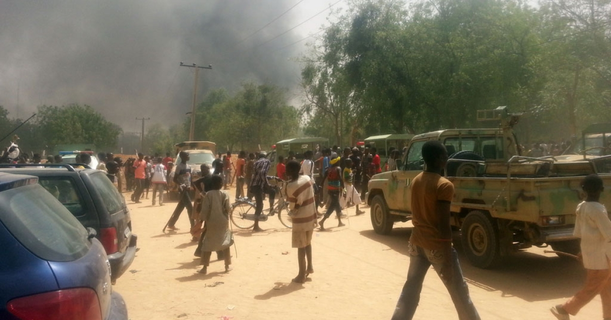 People walk in a street as smoke rises after Boko Haram Islamists attacked a military base in the northeast Nigerian city of Maiduguri on March 14, 2014.</p>