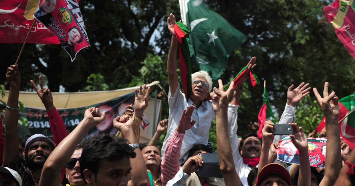 Pakistan supporters of cricketer-turned-politician Imran Khan cheer as he heads a protest march from Lahore to Islamabad against the government, in Lahore on Aug. 14, 2014.</p>
