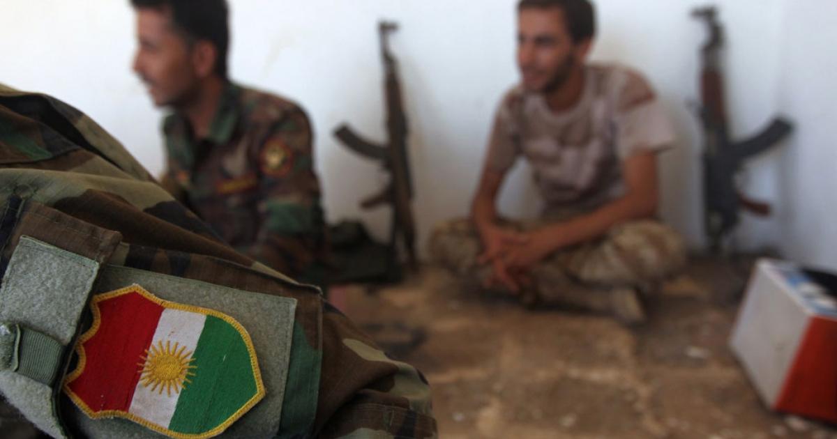 Iraqi Kurdish Peshmerga fighters rest on the front line in Bashiqa on Aug. 12, 2014.</p>
