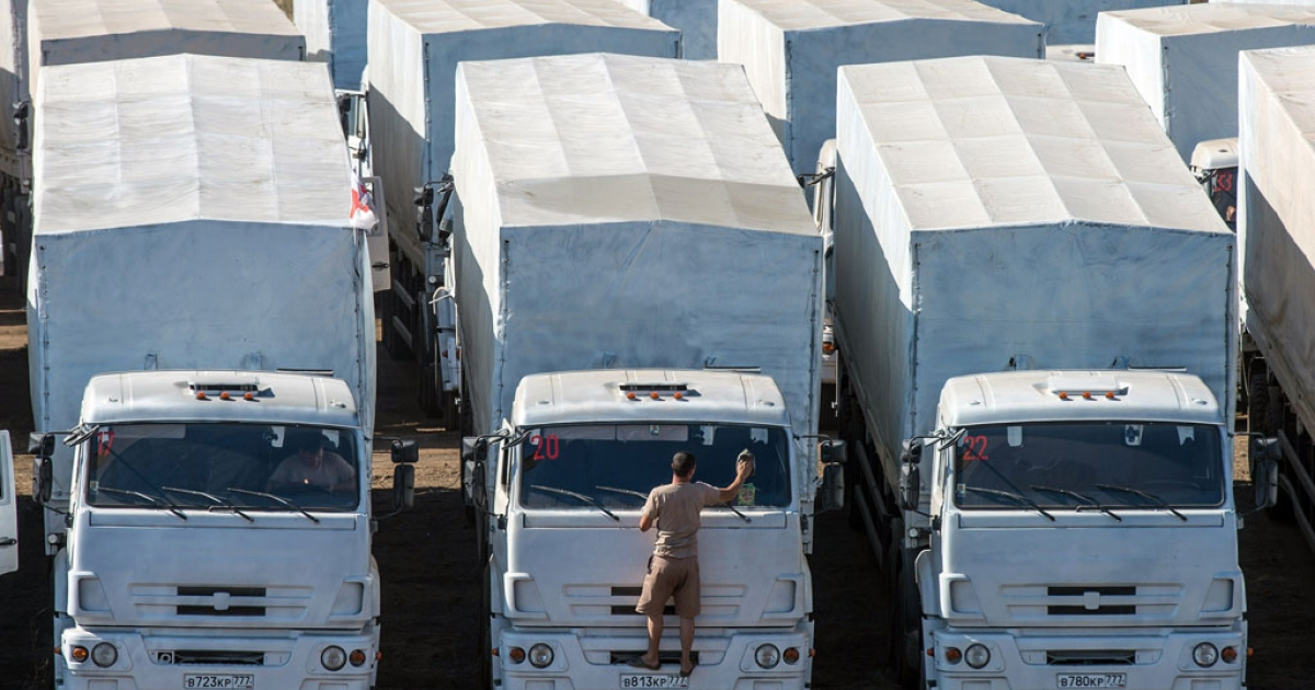 Trucks of Russian humanitarian convoy are parked in a field outside the town of Kamensk-Shakhtinsky in Rostov region, near the Russian-Ukrainian border, on Aug. 15, 2014.</p>