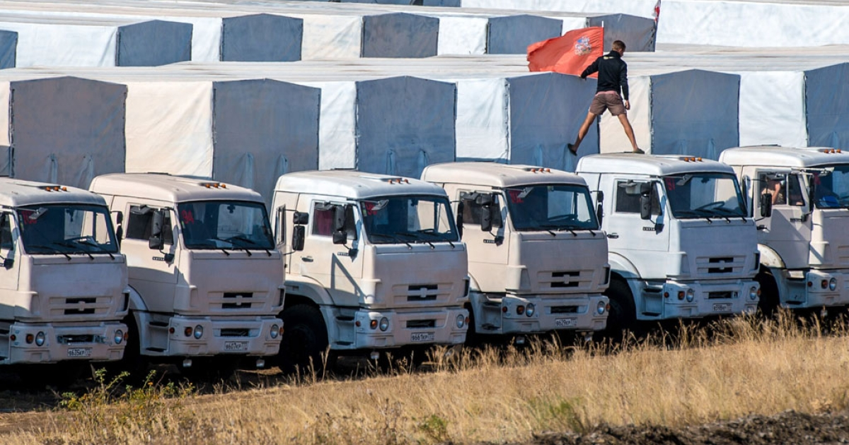 A driver installs a red flag on his lorry, parked with other lorries of the Russian humanitarian convoy not far from a checkpoint at the Ukrainian border in the Rostov region, on Aug. 20, 2014.</p>
