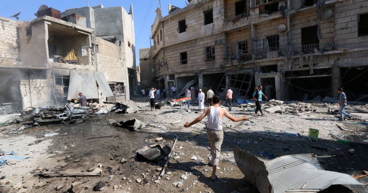 Syrians gather at the site of a reported barrel-bomb attack by government forces on Aug. 13, 2014, in the rebel-held Qadi Askar neighborhood in Aleppo.</p>