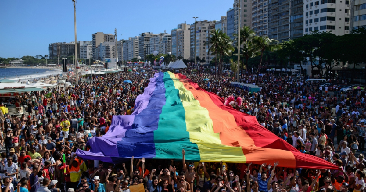 Revellers march with a giant rainbow flag during the annual Gay Pride Parade at Copacabana beach in Rio de Janeiro, Brazil, on November 16, 2014.</p>
