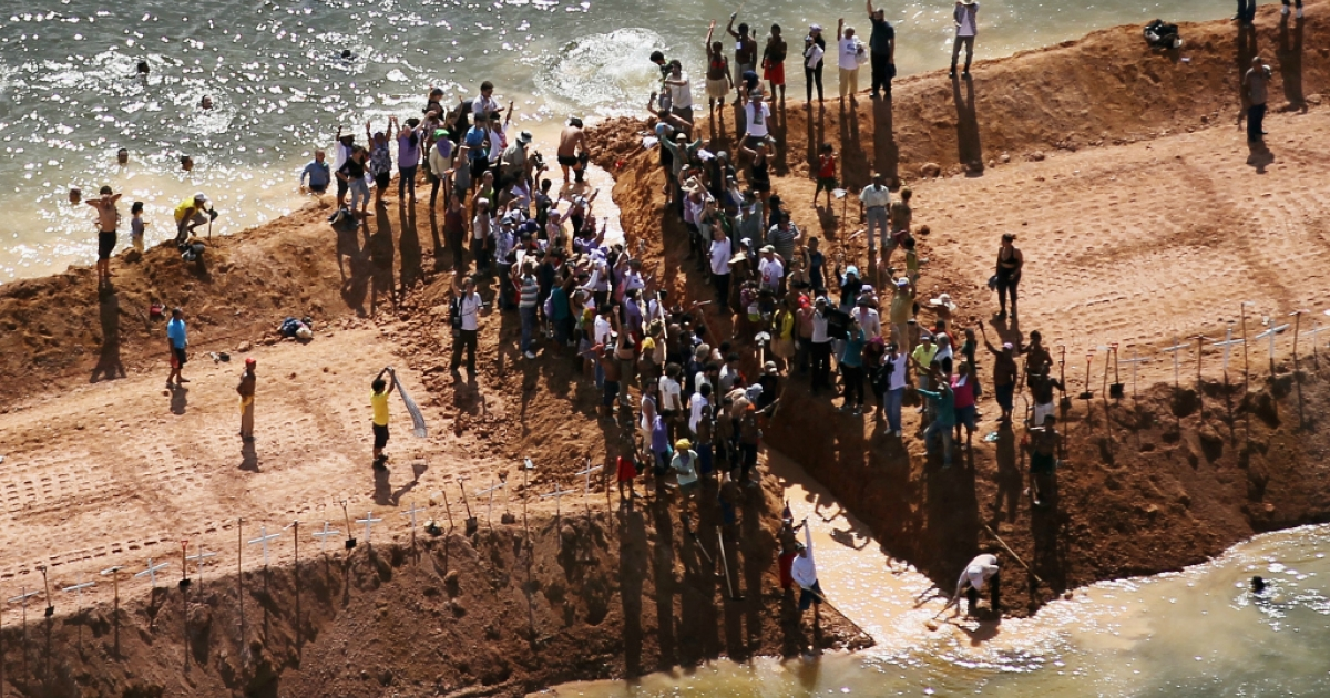 Residents who are being displaced by the Belo Monte dam and supporters stand atop a temporary earthen dam at the Belo Monte construction site after removing a strip of earth to restore the flow of the Xingu River as a protest against the construction on June 15, 2012 near Altamira, Brazil. Belo Monte will be the world's third-largest hydroelectric project and will displace up to 20,000 people while diverting the Xingu River and flooding as much as 230 square miles of rainforest. The controversial project is one of around 60 hydroelectric projects Brazil has planned in the Amazon to generate electricity for its rapidly expanding economy.</p>