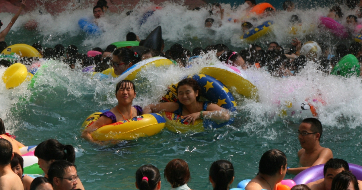 This picture taken on July 27, 2013 shows people trying to cool off at a water park in Suining, southwest China's Sichuan province, as a heatwave hit several provinces in China.</p>