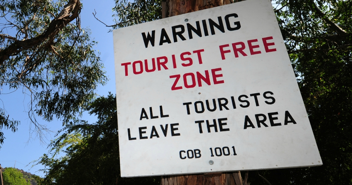 A placard warning of a 'Tourist Free Zone' is posted along a road often used by tourists and locals near Hollywood.</p>