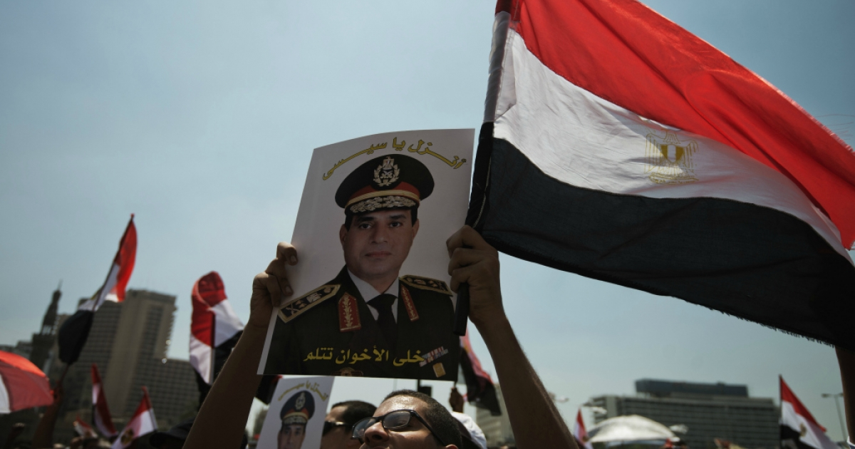 An Egyptian man holds a portrait of military chief General Abdel Fattah al-Sisi that reads in Arabic