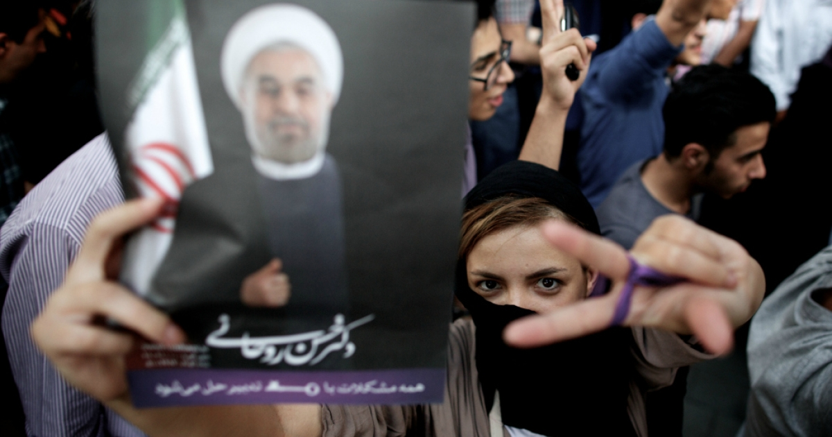 An Iranian woman flashes the sign for victory as she holds a portrait of moderate presidential candidate Hassan Rouhani during celebrations for his win in the Islamic Republic's presidential elections.</p>
