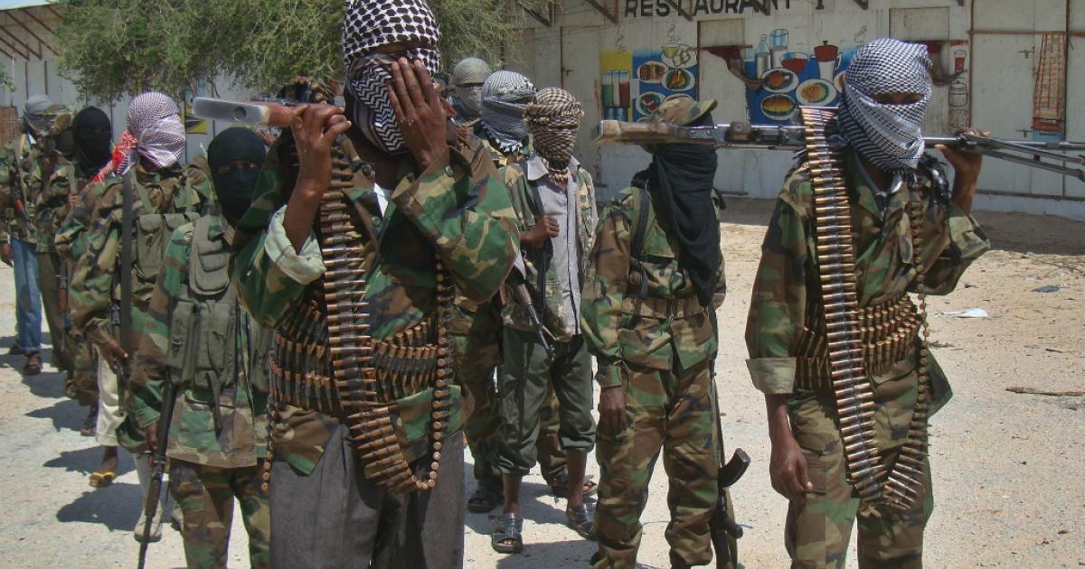 Al-Qaeda linked al-shabab recruits walk down a street in Mogadishu following their graduation.</p>