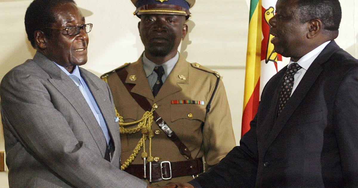 Zimbabwean President Robert Mugabe (L) shakes hands with Movement for Democratic Change leader Morgan Tsvangirai on July 21, 2008 in Harare after the signing of a deal between Zimbabwe's opposition and ruling party, paving the way for full-scale talks.</p>